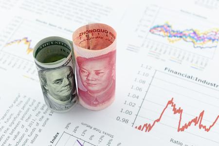 Gerolde rollen van Amerikaanse dollarbiljet en Chinese Yuan met afbeelding  portret van president Mao Zedong en Benjamin Franklin. Plaatsen op financiële rapporten met verschillende grafieken, dwz gekleurde lineaire grafiek.