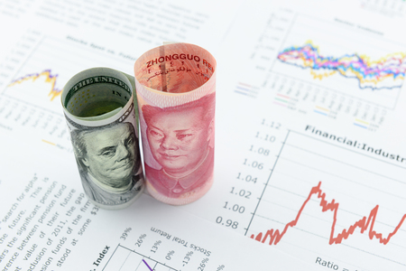 weaken: Rolled up scrolls of US dollar bill and Chinese Yuan with image  portrait of President Mao Zedong and Benjamin Franklin. Placing on financial reports with several charts i.e. colored linear graph. Stock Photo