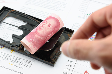 Rolled up scroll of CNY Chinese 100 yuan bill with portrait  image of Mao Zedong on a black rat trap. Using money as a bait to lure someone for illegal  dishonest things. China financial concept. Stock Photo