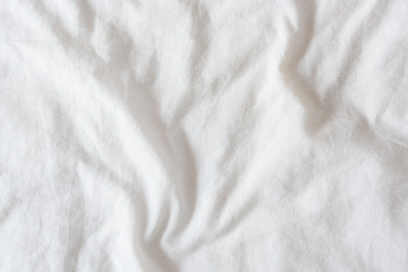 Top view of creased  wrinkles on a white unmade  messy bed sheet after waking up in the morning. Bedsheet is not neatly arranged for new guests or customers to sleep in. Abstract texture background