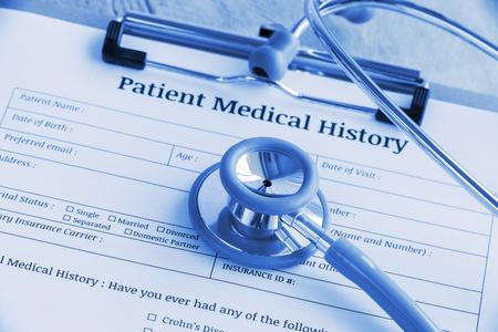 Geduldige medische geschiedenis op een klembord met stethoscoop en een blauwe ballpoint, die op de lijst van een arts zetten. Leeg formulier te wachten om te worden ingevuld en beoordeeld  onderzocht door verpleegkundige  klinisch assistent. Stockfoto
