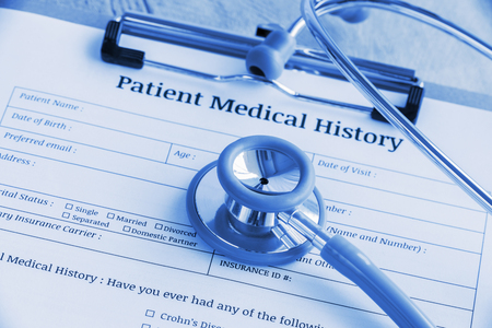 Patient medical history on a clipboard with stethoscope and a blue ballpoint pen, putting on a physician's table. Blank form waiting to be filled and reviewed / examined by nurse / clinical assistant. Standard-Bild