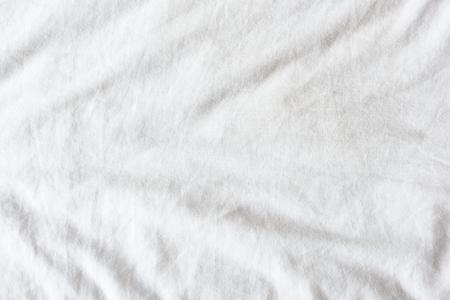 Bovenaanzicht van rimpels op een slordige wit laken in een slaapkamer na een lange nacht slapen en wakker worden in de ochtend.