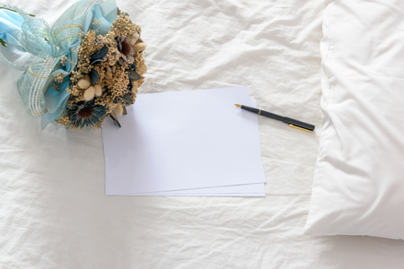Top view of blank papers with a fountain pen decorated with a bouquet of dried flowers on an unmade / untidy bed with a white pillow. Space for leaving messages / notes to someone in special occasions