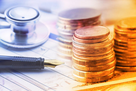 Stack of coins with a fountain pen and an chest-piece of a stethoscope on a table. A concept of healthcare expense which is very expensive due to inflation and the age of a patient, older pays higher. Stock Photo