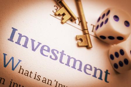 Vintage  retro-kleurstijl: twee koperen sleutels en dobbelstenen op een fundamenteel investeringsdocument. Een concept van het belangrijkste succes bij investeringen die enige basiskennis vereisen, anders zou het een gokspel zijn.
