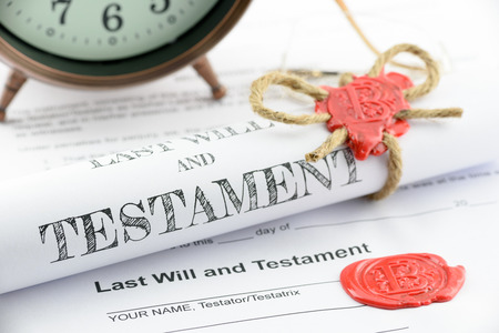 allegations: Rolled up scroll of last will and testament fastened with natural brown jute twine hemp rope, sealed with sealing wax and stamped with alphabet letter B. Decorated with an antique clock on a table. Stock Photo