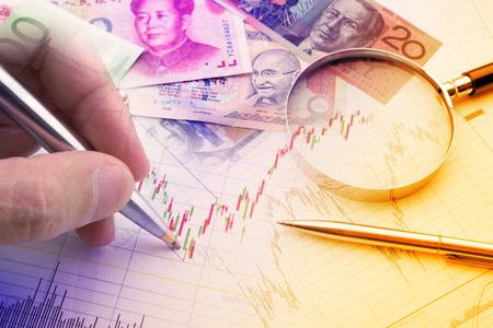 파란 볼펜을 들고 손을 금융 악기의 기술 차트를 분석입니다. 포트폴리오 수익을 극대화하려는 투자자를위한 외환  통화 거래 동향 분석의 개념.