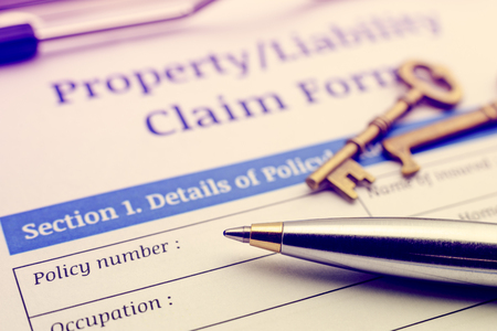 빈티지  레트로 색상 스타일 : 파란색 볼펜, 두 개의 골동품 황동 열쇠 및 클립 보드에 재산  책임 주장 양식. 보험 계약자가 작성하고 서명하기를 기