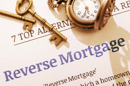 Vintage  retro kleur stijl met een lange schaduw: Twee messing sleutels en een zakhorloge op een omgekeerde hypotheek instructie document. Een concept voor een hypotheek die een ouderling die willen activa om te zetten in geld.
