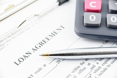 Blauwe balpen en een calculator op een leningsovereenkomst, voorbereiding voor het vullen van en het ondertekenen van een vorm op een klembord.