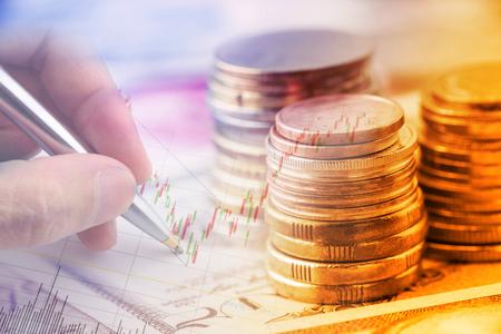 Close-up beeld: Stapel muntstukken en een hand met een balpen onderzoekt een technische grafiek van financieel instrument. Een idee  concept van de handel in valuta, het maken van een beslissing voor een optimale winst. Stockfoto