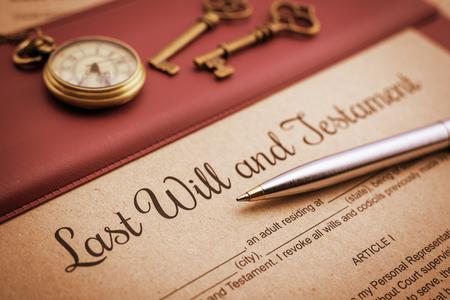estilo de la vendimia / retro: bolígrafo azul, reloj de bolsillo antiguo, dos llaves de latón y una última voluntad y testamento en un cojín de escritorio de vinilo. Una forma está a la espera de ser llenado y firmado por el testador / testadora.