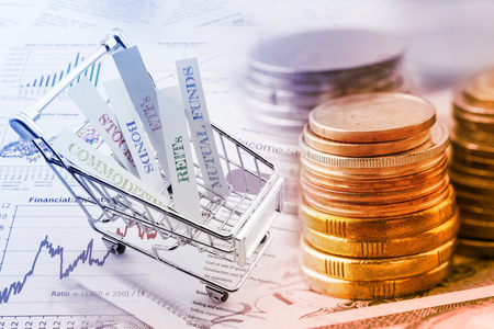 Stack of coins and a trolley with various types of financial investment products i.e. stocks, commodities, bonds, REITs, mutual funds, ETFs. Wealth management with risk diversification concept. Standard-Bild