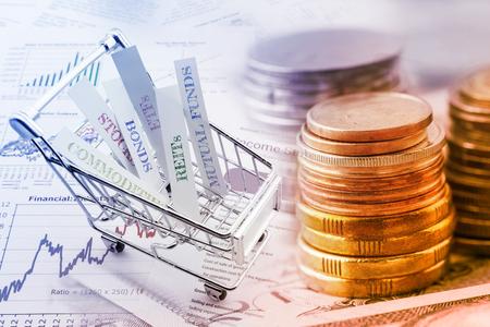Stapel munten en een trolley met diverse soorten financiële beleggingsproducten dwz aandelen, grondstoffen, obligaties, REIT's, beleggingsfondsen, ETF's. Vermogensbeheer met risicospreiding concept.
