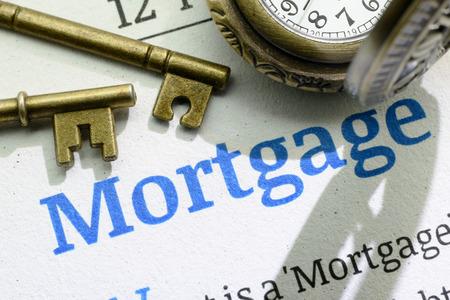Twee vintage koperen sleutels en een zakhorloge op een fundamentele hypotheek handleiding. Een idee  concept van leningen waarbij een huiseigenaar moet weten voordat contracten  verplichtingen worden ondertekend.