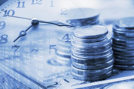 Closeup widok: Stos monet i zegar ręce. Koncepcja / idea wartości pieniądza w czasie. Pieniądze w chwili obecnej jest warta więcej niż ta sama kwota w przyszłości ze względu na jego potencjalne możliwości zarobkowych. Zdjęcie Seryjne