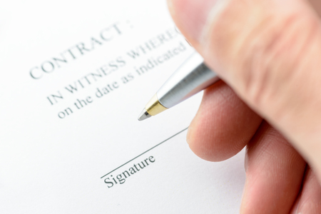 A man with a ballpoint pen in his right hand, preparation for signing a contract.