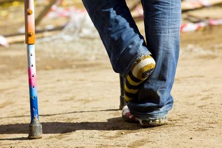 color crutch and broken leg in striped sock photo