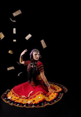 woman in traditional indian costume againist falling money studio shot photo