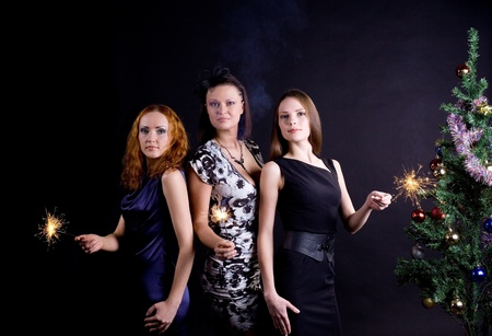 Three girls and christmas tree with bengal light Stock Photo - 8533802