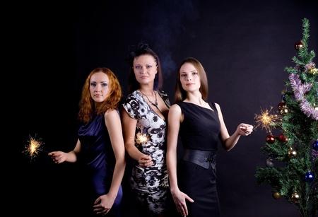 Three girls and christmas tree with bengal light Stock Photo - 8533802