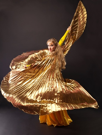 Beauty mature woman dance with gold wing arabian style photo