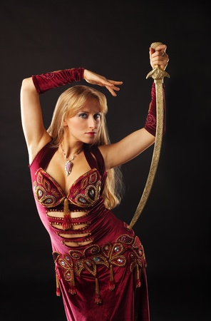 Beauty arabian dancer with saber on hip look at you photo