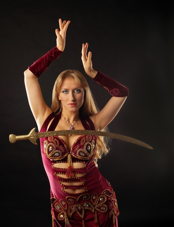 Beauty arabian dancer with saber on breast photo