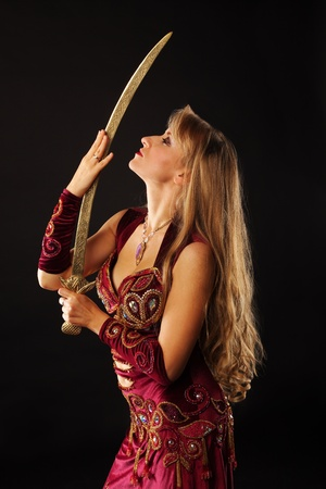 Beauty mature arabian dancer with saber look on it Stock Photo - 8601743