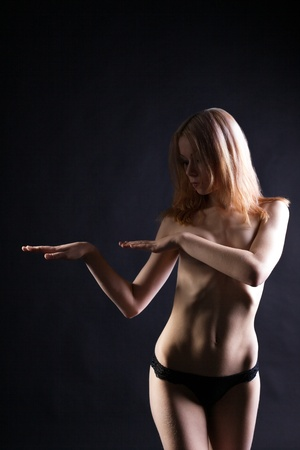 Young blonde naked woman dance in dark Stock Photo - 8663128