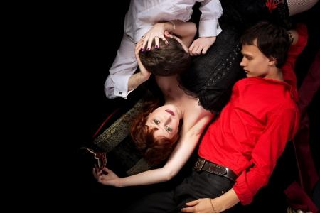 gelosia: Donna rossa e due uomini love triangle - stile di decadenza