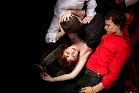 decadence: red woman and two men love triangle - decadence style Stock Photo