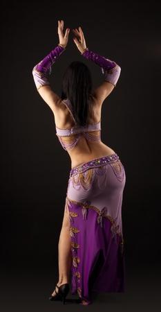 Woman dance in traditional purple arabian costume photo
