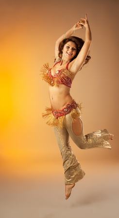 woman jump in belly dance with finger cymbals photo
