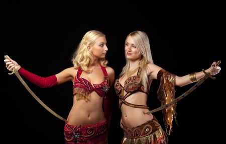 Two blond girl stand with saber - arabian costume photo