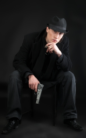Man with pistol sit in black cloth look at you photo