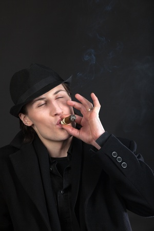 Man in black cloth and hat smoke cigar with taste photo