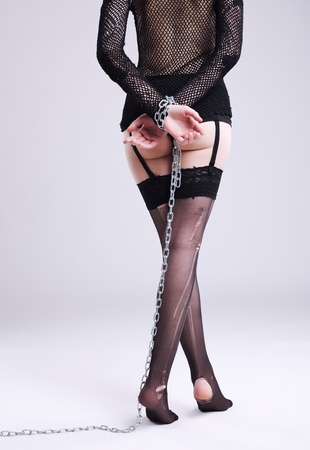 Legs in lingeries with chain on hands - bdsm style Stock Photo