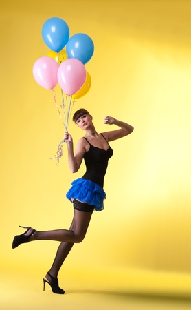 pretty woman with balloons pinup style on yellow Stock Photo - 8872404