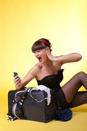 Young woman with broken baggage scream on cell - pinup photo