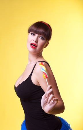 Beauty woman with lollipop pinup style on yellow Stock Photo - 8872417