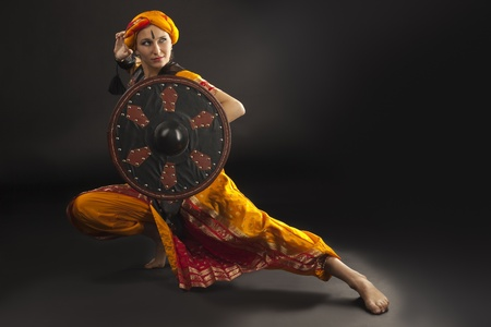 traditional weapon: Beauty woman posing with shield - arabian costume