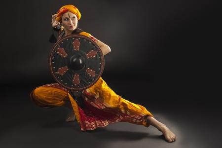 Beauty woman posing with shield - arabian costume