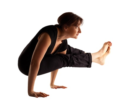 Mature woman stand on hands  in yoga pose isolated photo