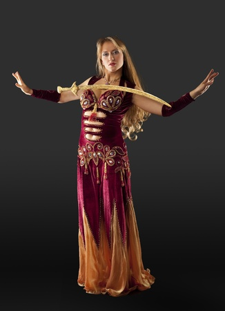 Beauty blond arabian dancer stand with saber on breast photo