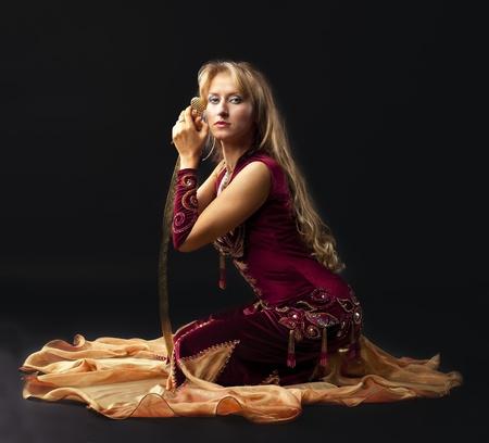 Beauty arabian dancer sit with saber on black background photo