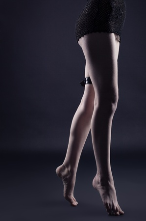 Woman legs in dark with leather belt - gothic style photo
