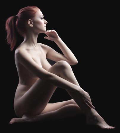 femme se deshabille: Jeune fille posant dans dark - fermer son corps Banque d'images