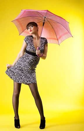 sexy woman posing with rose umbrella pin-up style on yellow photo